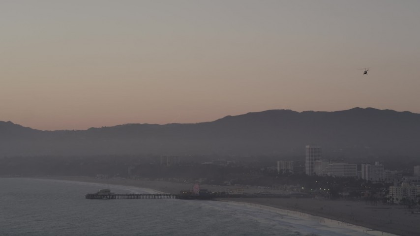 5K stock footage aerial video tilt from helicopter to reveal Santa Monica Pier at sunset, California Aerial Stock Footage | AX69_027