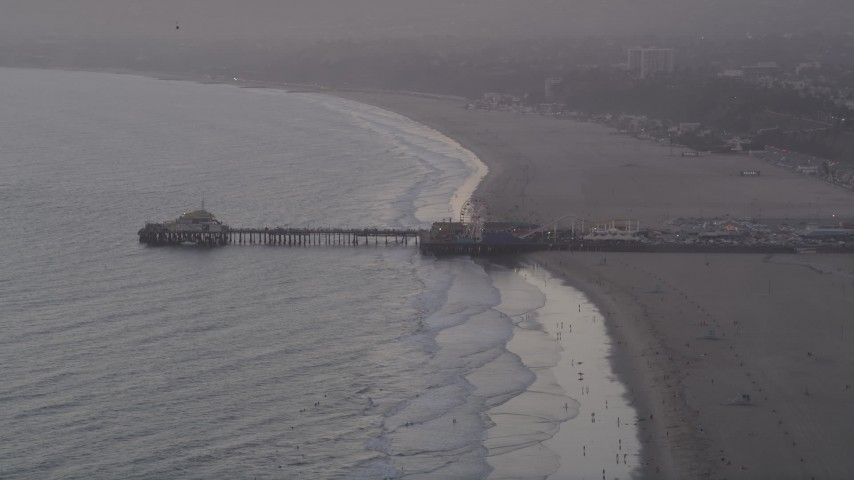 5K stock footage aerial video of Santa Monica Pier at sunset and people walking the beach, California Aerial Stock Footage | AX69_028