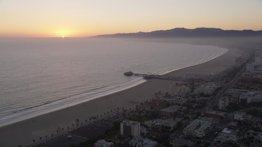 5K stock footage aerial video of the Santa Monica Pier with the sun setting in the horizon, California Aerial Stock Footage | AX69_030