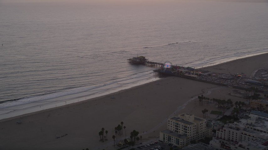 Approaching Santa Monica Pier and Pacific Wheel at sunset, California Aerial Stock Footage | AX69_032