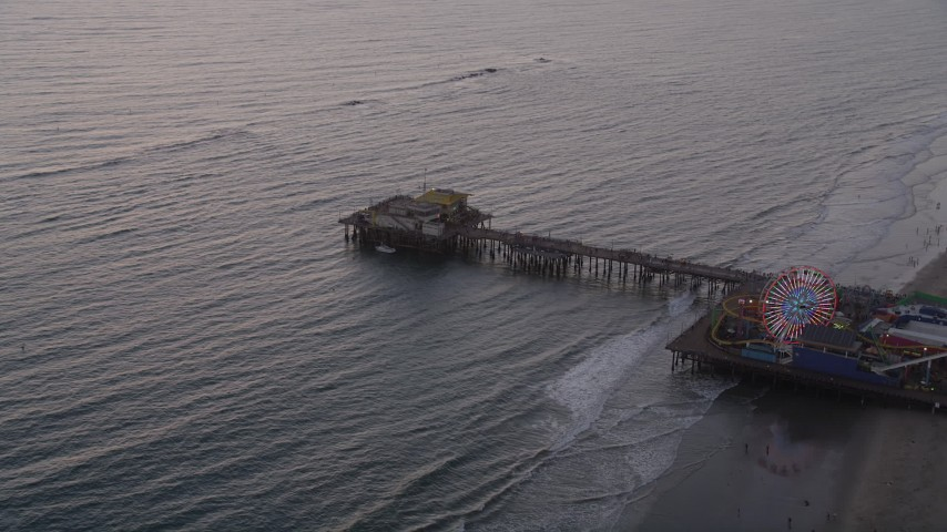 Approach and Pan Across the End of Santa Monica Pier at Sunset Aerial Stock Footage | AX69_033
