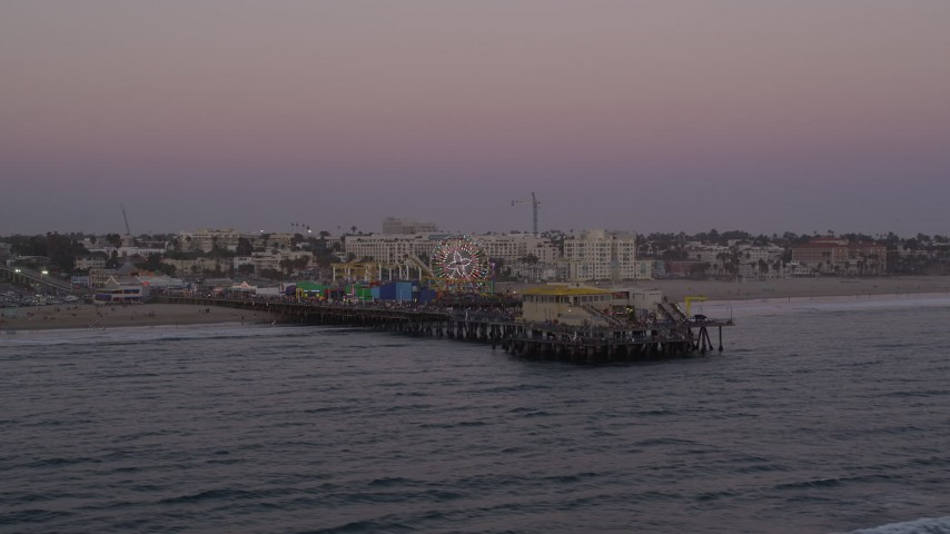 Orbit and fly away from the end of Santa Monica Pier at twilight, California Aerial Stock Footage | AX69_036