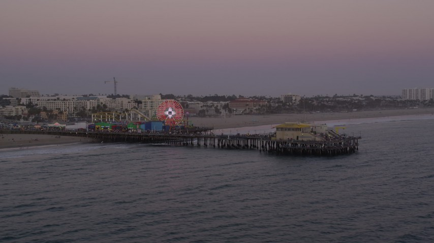 5K stock footage aerial video orbit and fly away from the end of Santa Monica Pier at twilight, California Aerial Stock Footage | AX69_036