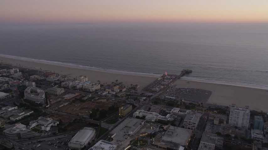 Flyby beachside buildings and Santa Monica Pier at sunset, California Aerial Stock Footage | AX69_038