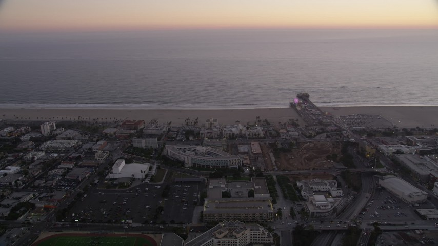 5K stock footage aerial video orbit buildings by the beach and Santa Monica Pier at twilight, California Aerial Stock Footage | AX69_039