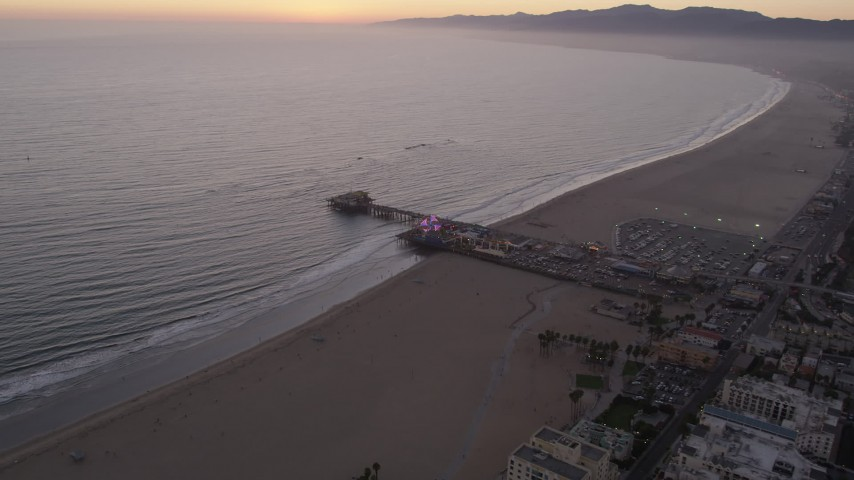 5K stock footage aerial video fly over the beach and by the end of Santa Monica Pier at twilight, California Aerial Stock Footage | AX69_041