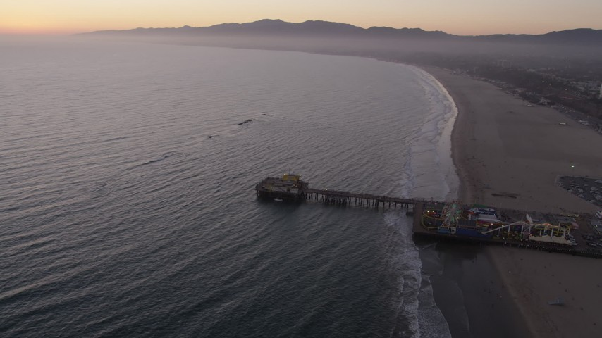 The end of Santa Monica Pier, Pacific Wheel, and the beach at sunset, California Aerial Stock Footage | AX69_042