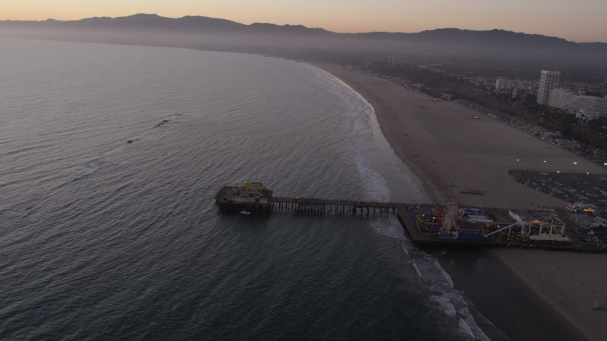 5K stock footage aerial video of the end of Santa Monica Pier, Pacific Wheel, and the beach at twilight, California Aerial Stock Footage | AX69_042