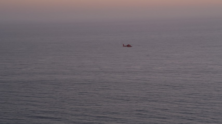 5K stock footage aerial video of tracking a Coast Guard helicopter over the Pacific Ocean at twilight Aerial Stock Footage | AX69_043