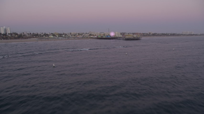 5K stock footage aerial video tilt from the ocean to reveal and approach Santa Monica Pier at twilight, California Aerial Stock Footage | AX69_046
