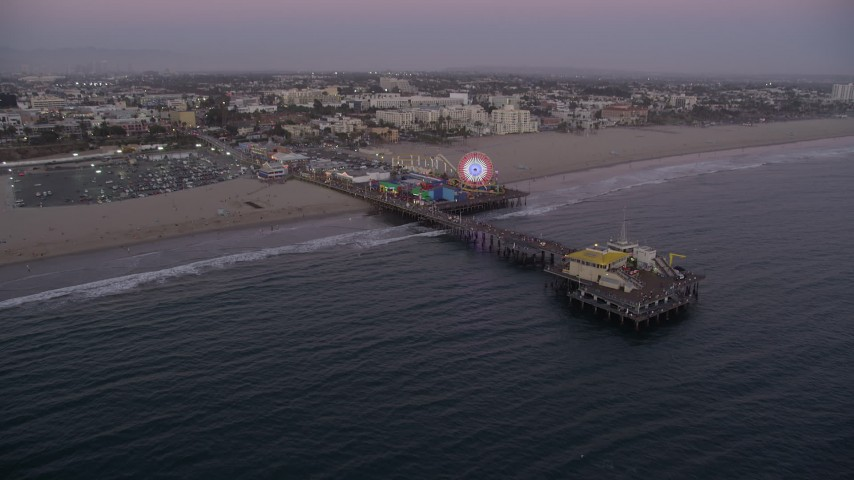 5K stock footage aerial video approach Santa Monica Pier at twilight and tilt to a bird's eye view, California Aerial Stock Footage | AX69_047
