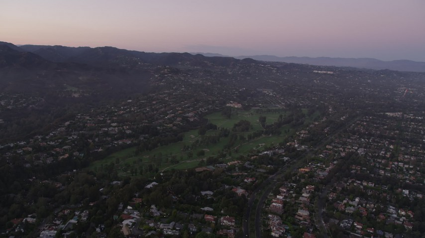 5K stock footage aerial video approach a golf course and mansions at sunset in Pacific Palisades, California Aerial Stock Footage | AX69_048