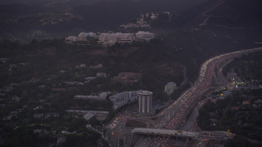 5K stock footage aerial video of J. Paul Getty Museum, Hotel Angeleno, and I-405 with heavy traffic at twilight, Brentwood, California Aerial Stock Footage | AX69_054