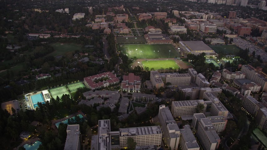 Orbit UCLA sports fields and campus buildings at twilight, Westwood, California Aerial Stock Footage | AX69_055