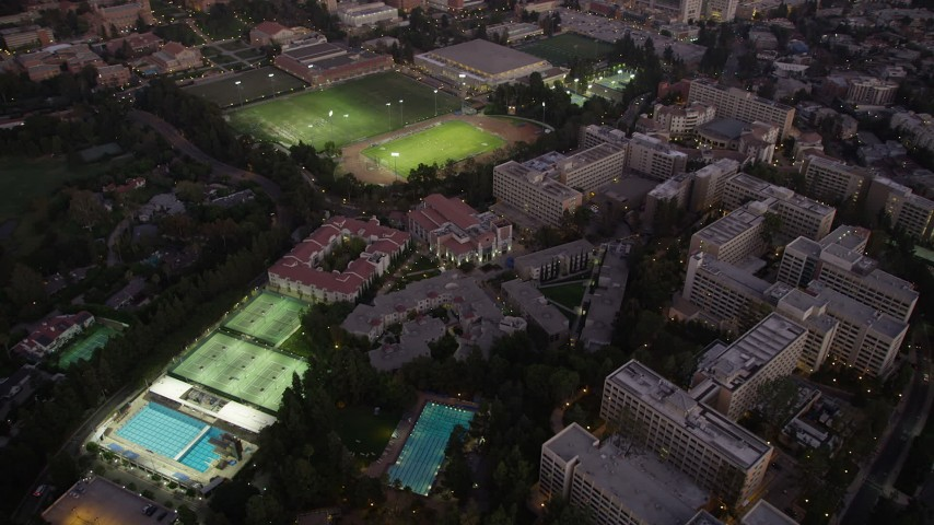 Orbit of campus buildings and sports fields at twilight at UCLA, Westwood, California Aerial Stock Footage | AX69_056