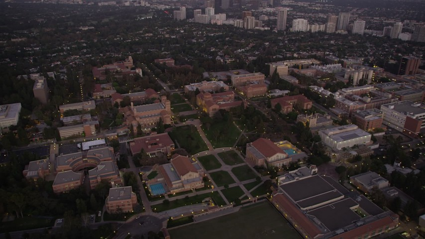 Fly over Wilson Plaza, Dickson Court, and UCLA campus buildings at twilight, Westwood, California Aerial Stock Footage | AX69_058