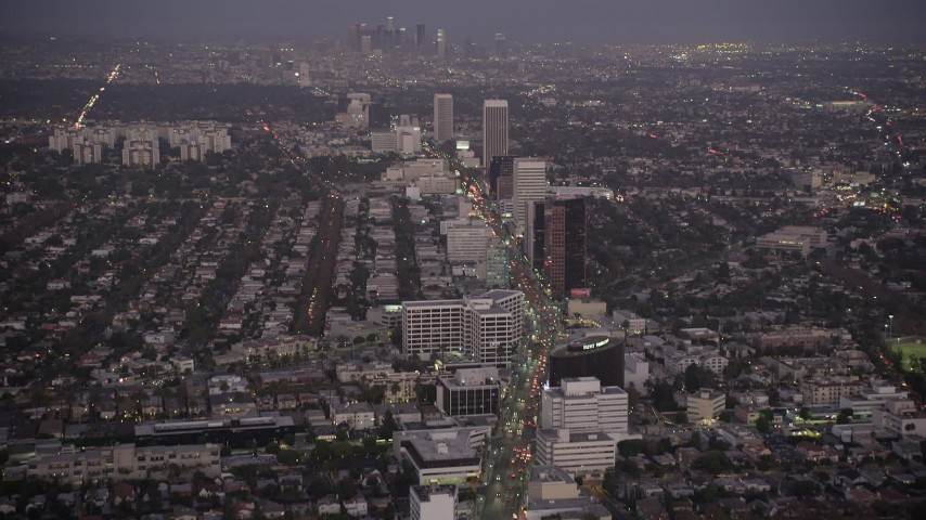 Tilt from Wilshire Boulevard in Beverly Hills to reveal Downtown Los Angeles, California, twilight Aerial Stock Footage | AX69_069