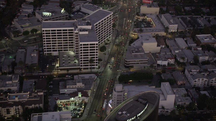 Fly over office buildings on Wilshire Boulevard in Beverly Hills, California, twilight Aerial Stock Footage | AX69_070