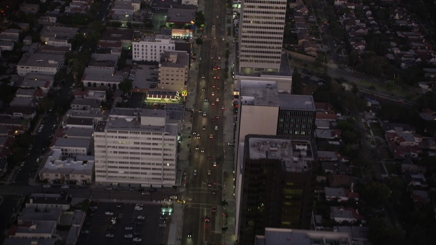 5K stock footage aerial video follow Wilshire Boulevard past office buildings in Beverly Hills, California, twilight Aerial Stock Footage | AX69_071