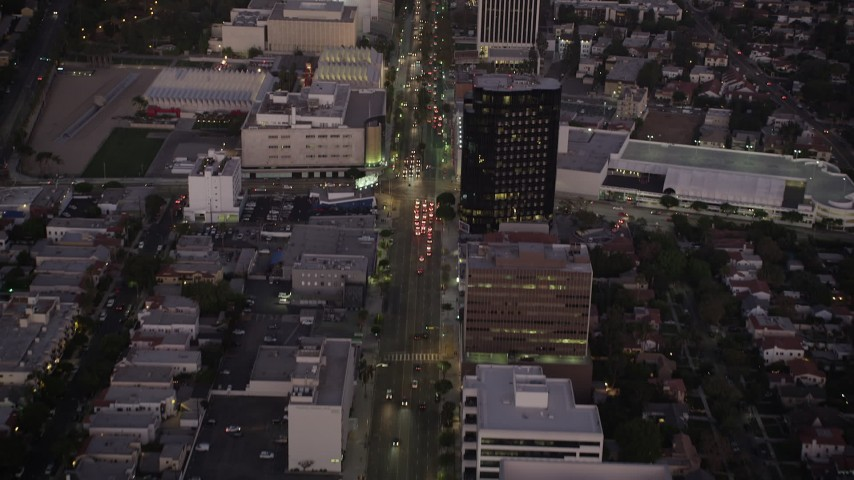Tilt from Wilshire Boulevard in Beverly Hills to reveal Downtown Los Angeles Skyline at twilight, California Aerial Stock Footage   AX69_072