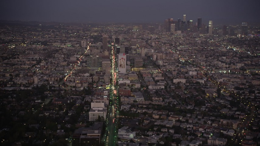 5K stock footage aerial video tilt from Wilshire Boulevard to reveal Koreatown and Downtown LA skyline at night, California Aerial Stock Footage | AX69_075