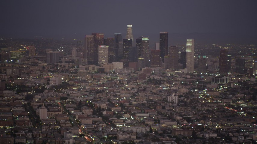 Tilt from apartment buildings to reveal and approach Downtown Los Angeles at night, California Aerial Stock Footage | AX69_076
