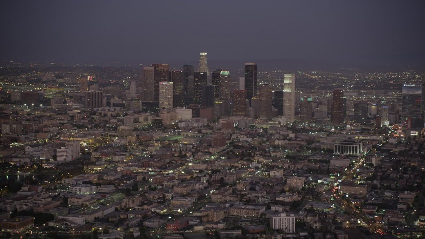 5K stock footage aerial video tilt from apartment buildings and city street to reveal Downtown Los Angeles skyline at night, California Aerial Stock Footage | AX69_077