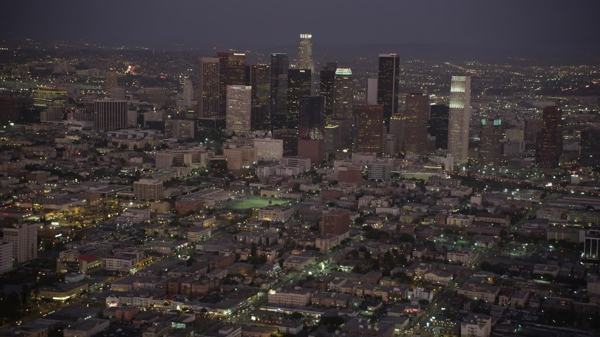 5K stock footage aerial video tilt from urban streets and apartments to reveal and approach the Downtown Los Angeles skyline at night, California Aerial Stock Footage | AX69_078