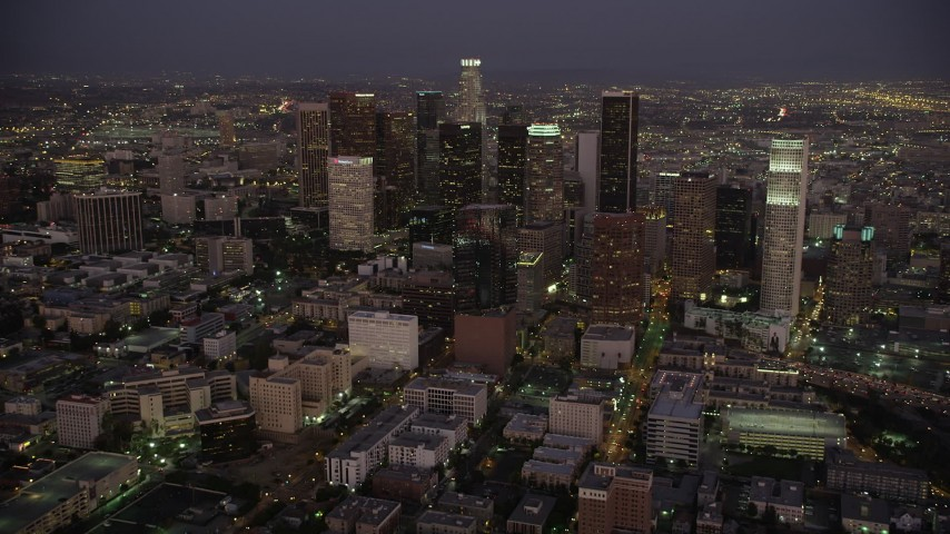 5K stock footage aerial video tilt from urban apartment buildings to reveal and approach Downtown Los Angeles at night, California Aerial Stock Footage | AX69_080