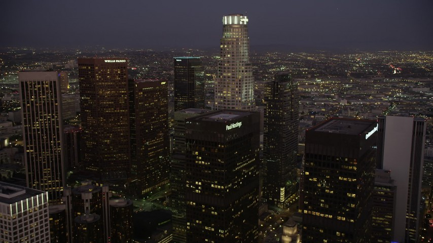 Fly over Paul Hastings Tower to approach US Bank Tower in Downtown Los Angeles, California at night Aerial Stock Footage | AX69_082