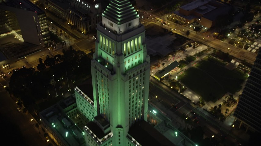 5K stock footage aerial video tilt from street to reveal Los Angeles City Hall in Downtown Los Angeles at night, California Aerial Stock Footage | AX69_086