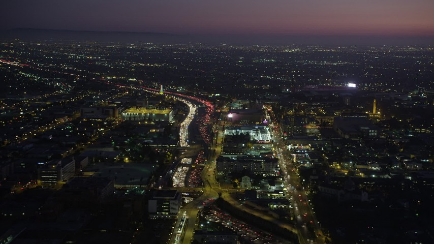 Heavy traffic on Interstate 110 by University Park, Los Angeles, California at night Aerial Stock Footage | AX69_095