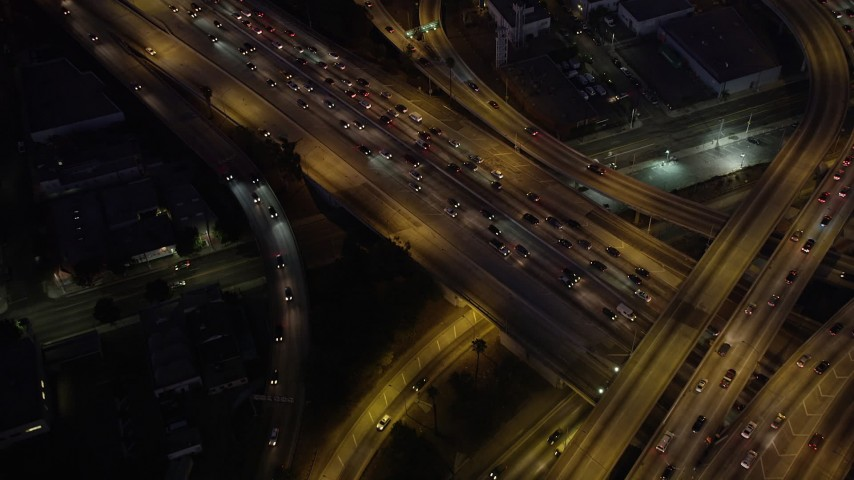 Bird's eye view of the I-110 / 10 interchange in Downtown Los Angeles, California at night Aerial Stock Footage | AX69_097