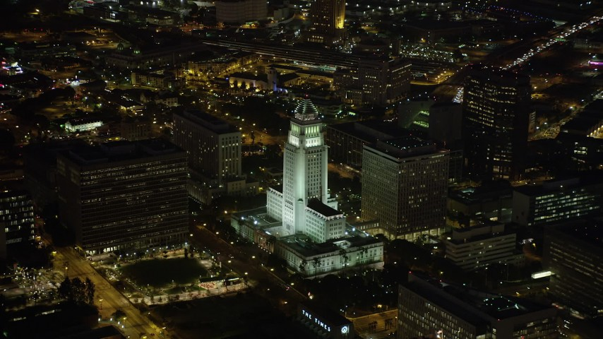 Los Angeles City Hall and courthouse in Downtown Los Angeles, California at nighttime Aerial Stock Footage | AX69_120