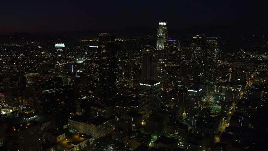 A view of US Bank Tower and skyscrapers in Downtown Los Angeles, California at night Aerial Stock Footage | AX69_129