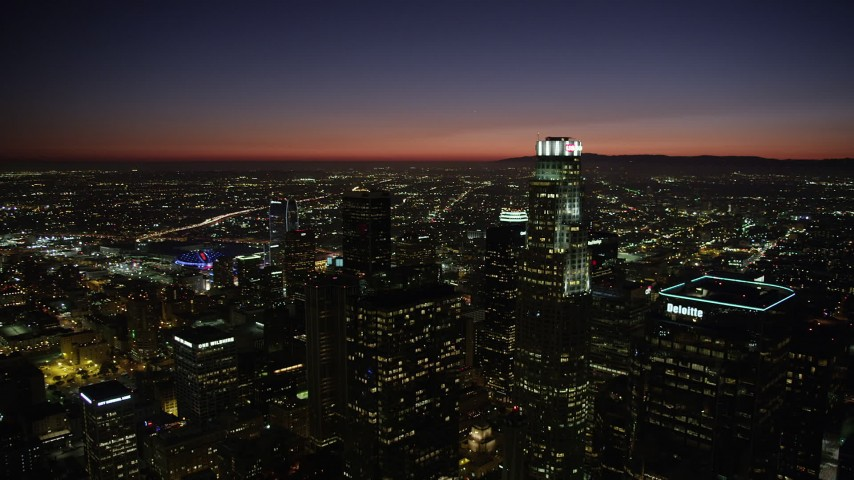 Reverse view of the towers of Downtown Los Angeles at nighttime, California Aerial Stock Footage | AX69_132