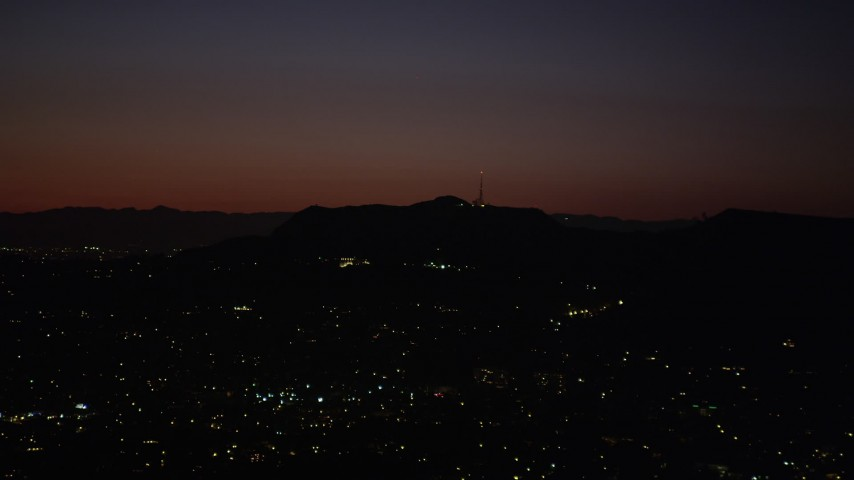 Radio tower and the lights of homes atop the Hollywood Hills at night, California Aerial Stock Footage AX69_135