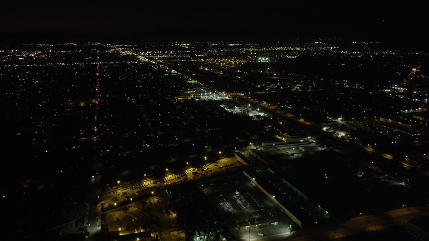 5K stock footage aerial video tilt to reveal suburban Pacoima neighborhoods and Whiteman Airport at night, California Aerial Stock Footage | AX69_153