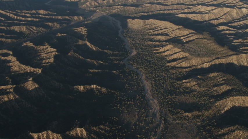 4K stock footage aerial video Dry riverbed between mountain ridges in Los Padres National Forest at sunrise, California Aerial Stock Footage   AX70_022