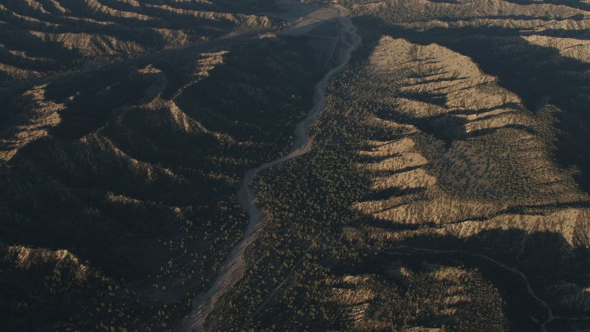 4K stock footage aerial video of A view of a dry riverbed between mountain ridges in Los Padres National Forest at sunrise, California Aerial Stock Footage | AX70_023