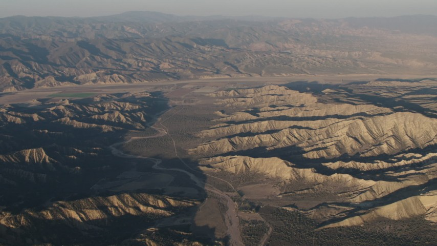 4K stock footage aerial video Farms beyond a dry riverbed between rugged mountain ridges at sunrise, Cuyama, California Aerial Stock Footage | AX70_027