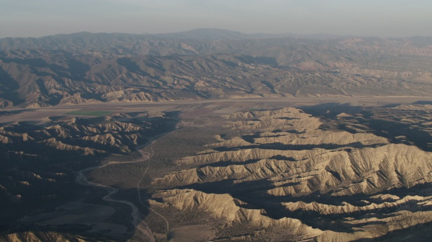 4K stock footage aerial video Dry riverbed between mountain ridges near farms at sunrise, Cuyama, California Aerial Stock Footage AX70_028 | Axiom Images