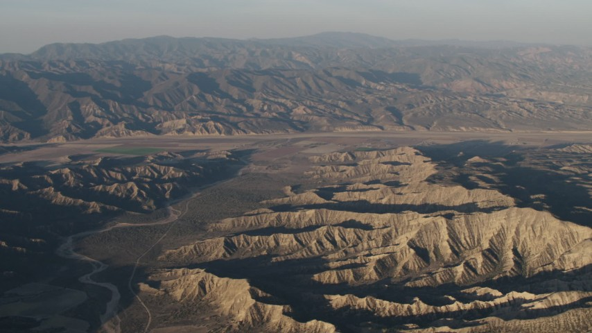 4K stock footage aerial video Dry riverbed and mountain ridges near farms at sunrise, Cuyama, California Aerial Stock Footage | AX70_029