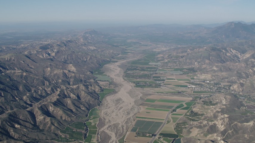 4K stock footage aerial video Farm fields and Santa Clara River bordered by mountains in Piru, California Aerial Stock Footage | AX70_183