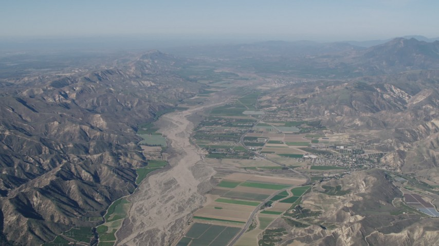 4K stock footage aerial video Farm fields and Santa Clara River surrounded by mountains in Piru, California Aerial Stock Footage | AX70_184