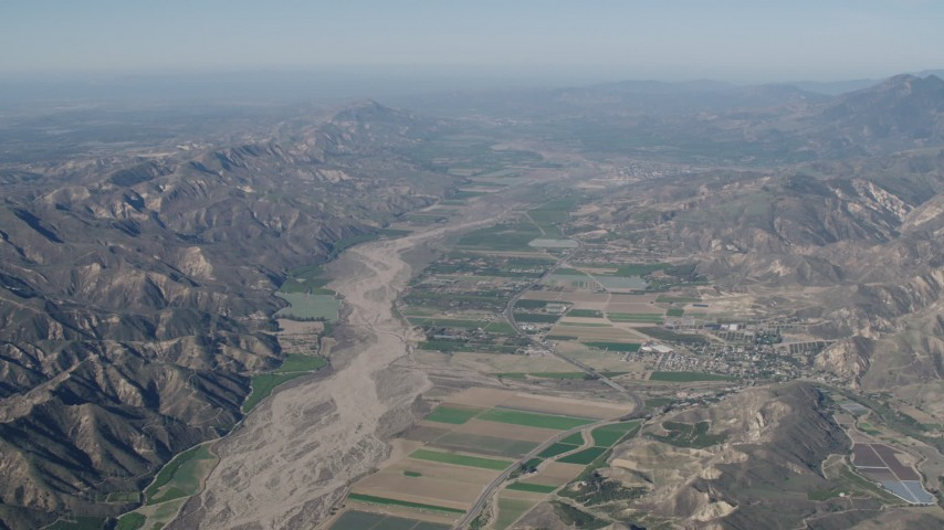 4K stock footage aerial video Flyby farm fields and Santa Clara River surrounded by mountains in Piru, California Aerial Stock Footage | AX70_185