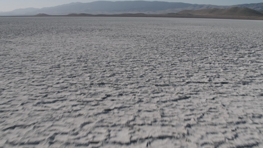 4K stock footage aerial video Fly low over Soda Lake in California, and tilt to reveal desert mountains Aerial Stock Footage | AX70_216