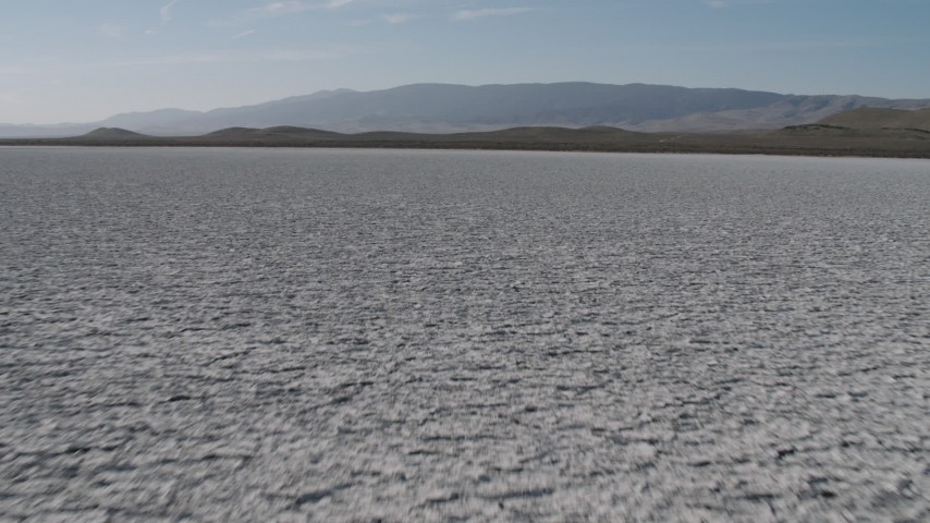 4K stock footage aerial video low altitude flight over Soda Lake in California toward a desert mountain range Aerial Stock Footage | AX70_220