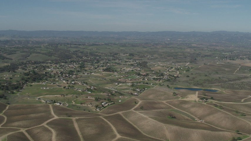 4K stock footage aerial video Passing rural homes, vineyards, and a pond in Paso Robles, California Aerial Stock Footage | AX70_224