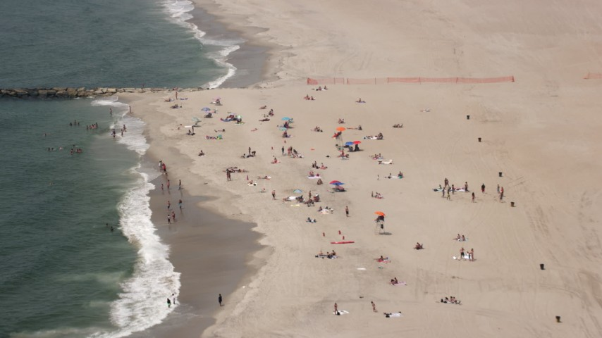 5K stock footage aerial video flying over beach goers at Rockaway Beach, Queens, New York Aerial Stock Footage | AX71_033